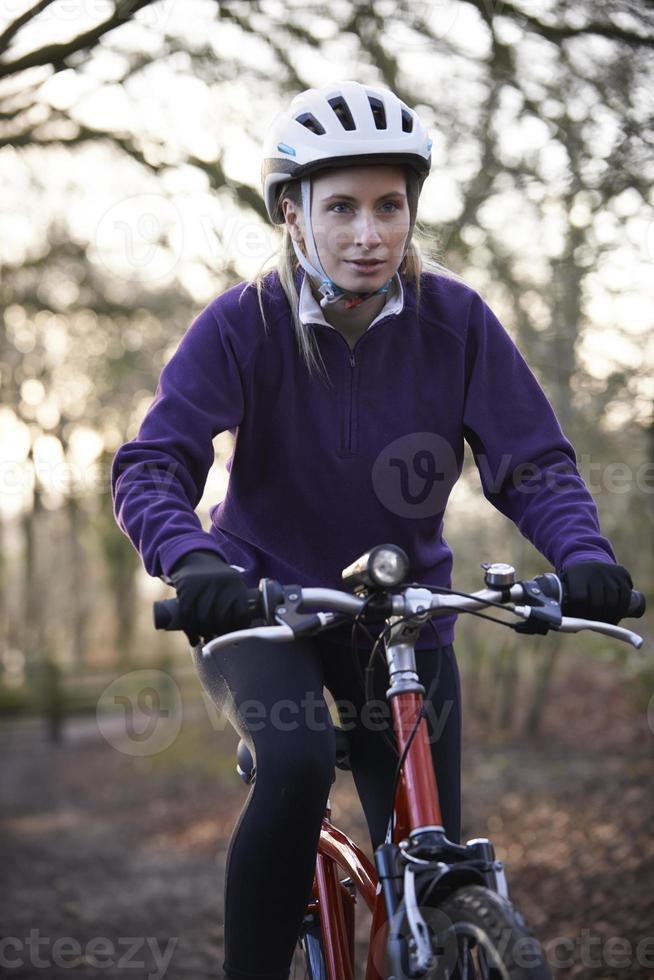 kvinna ridning mountainbike genom skogsmark foto