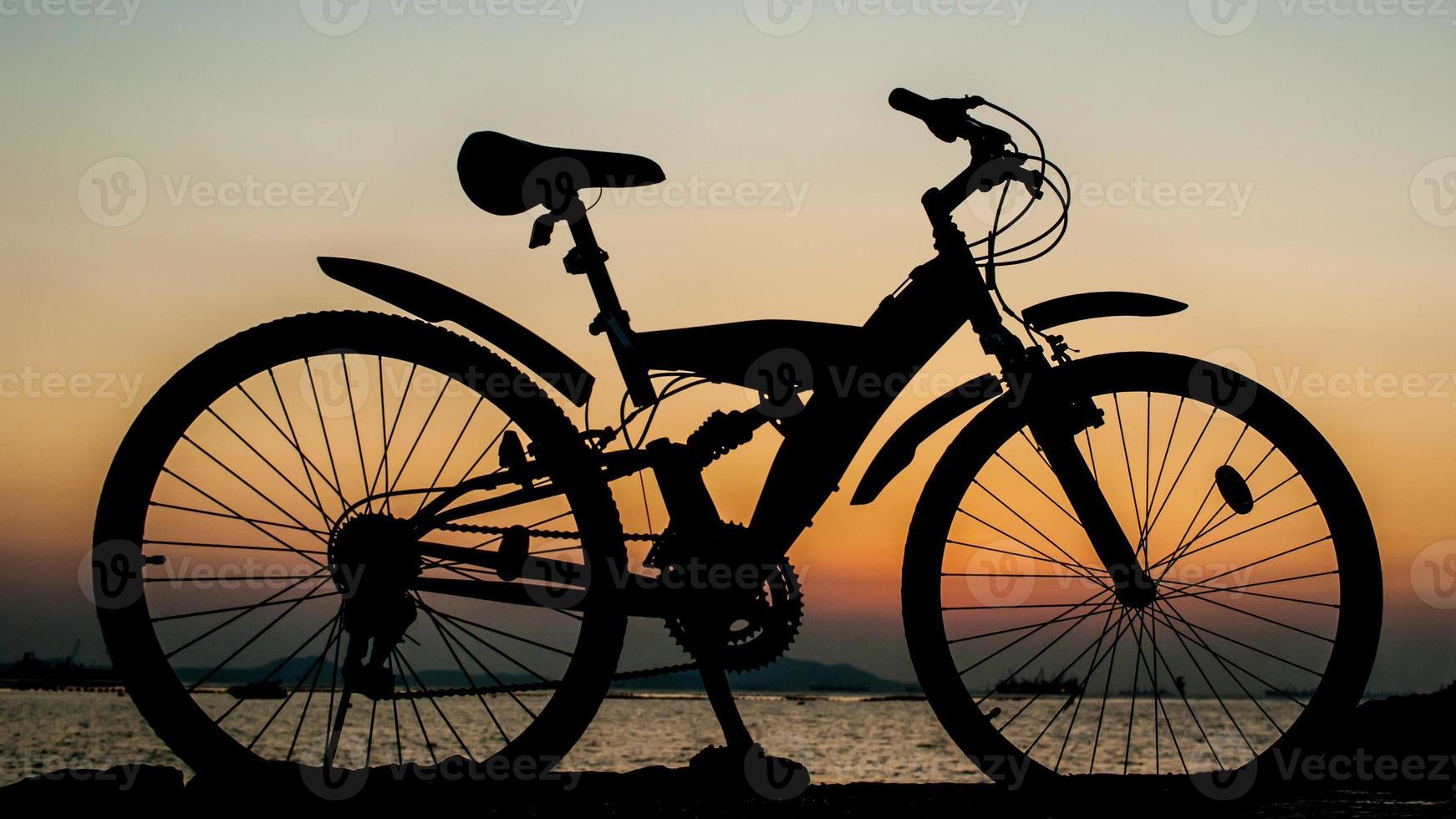 silhuett av mountainbike parkering på brygga bredvid havet foto