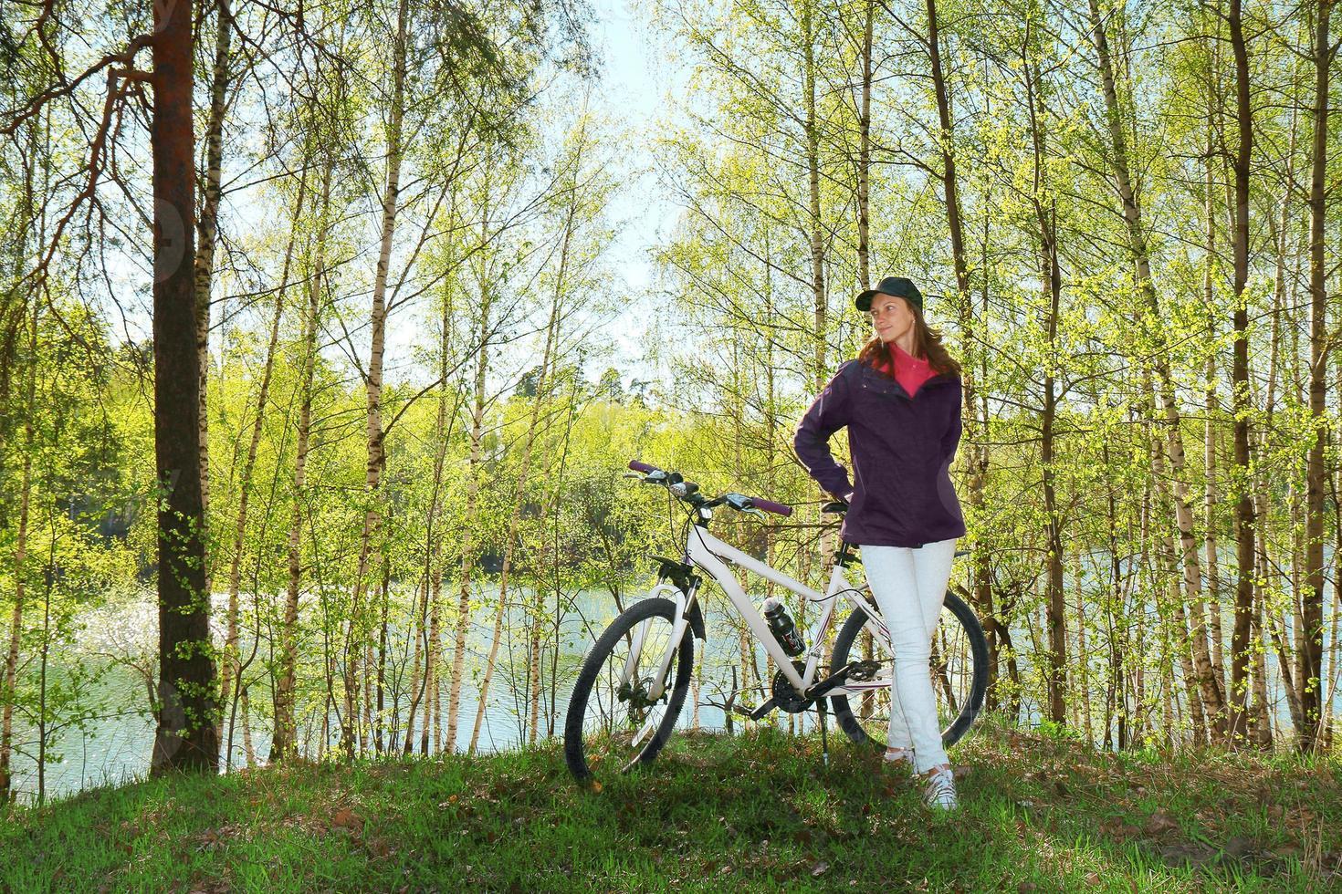 kvinna på cykel i skogen foto