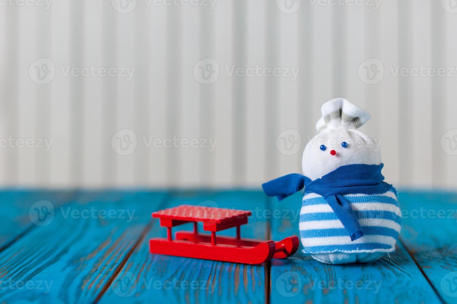 röd släde och lite handgjord snögubbe på ljus träbakgrund foto