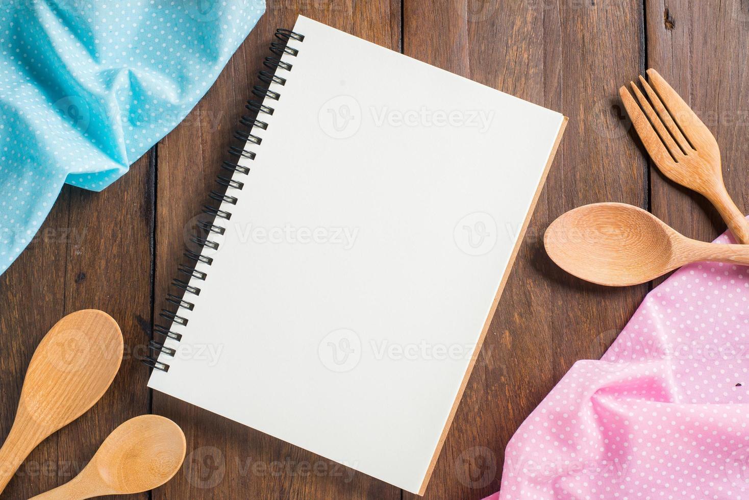 recept anteckningsbok, sked, gaffel på trä bakgrund foto