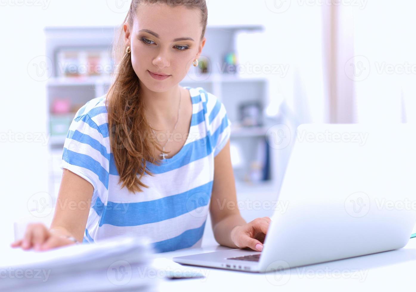 kvinna med dokument som sitter på skrivbordet foto