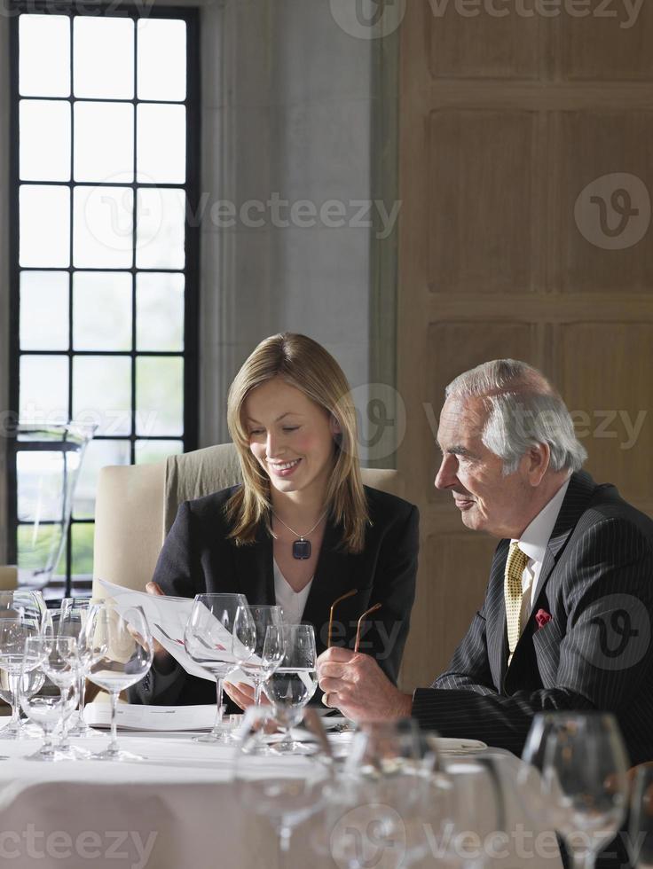 affärsman och kvinna som läser dokument vid restaurangbordet foto