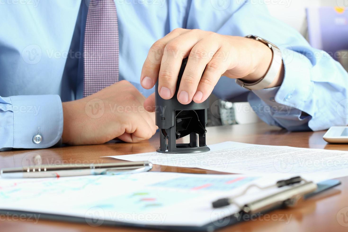 närbild av affärsman hand trycka på en stämpel på dokument foto