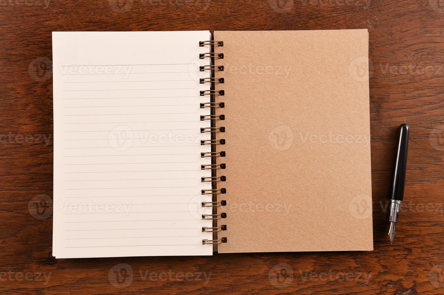 öppen anteckningsbok och penna foto