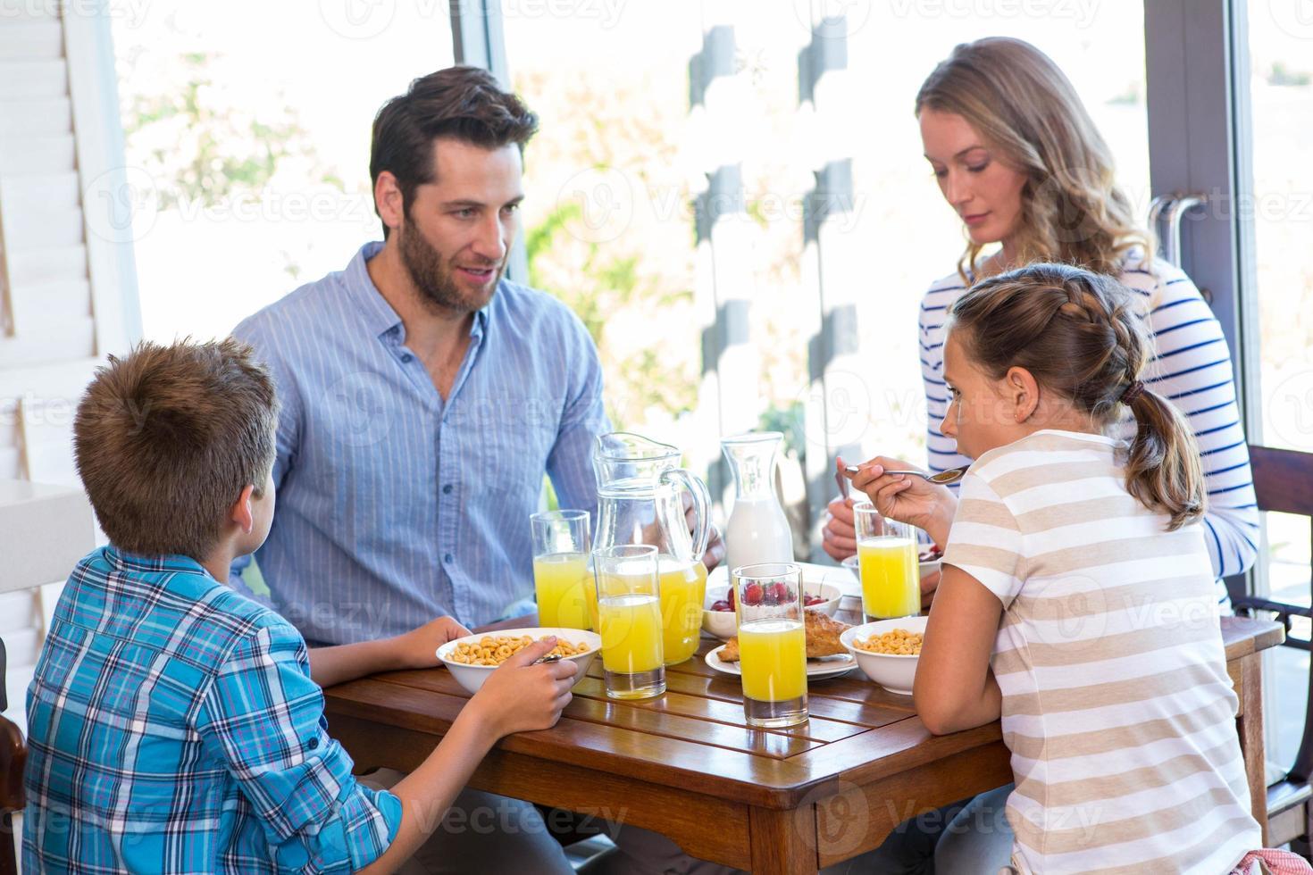 lycklig familj som äter frukost tillsammans foto