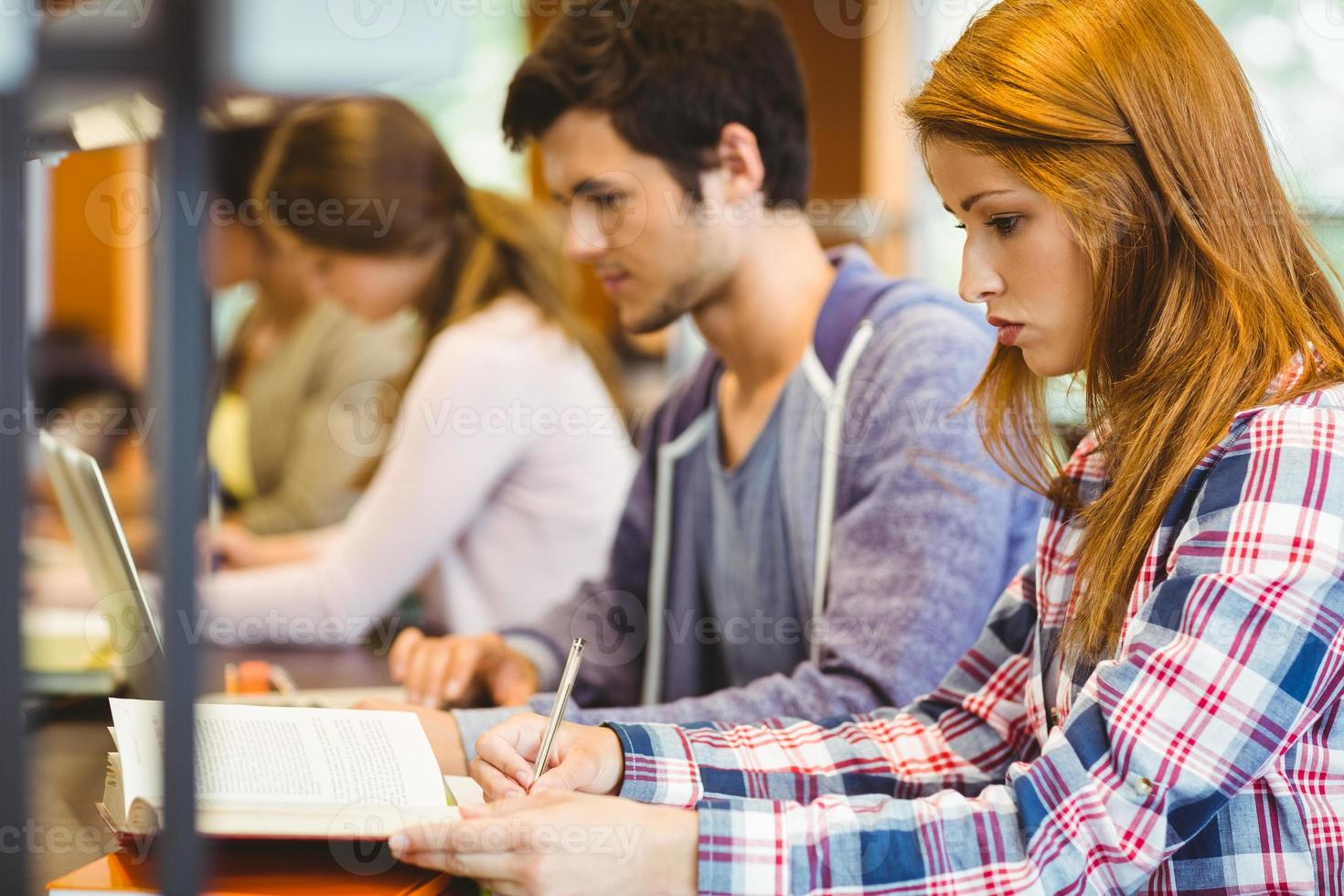 fyra fokuserade klasskamrater som arbetar tillsammans foto
