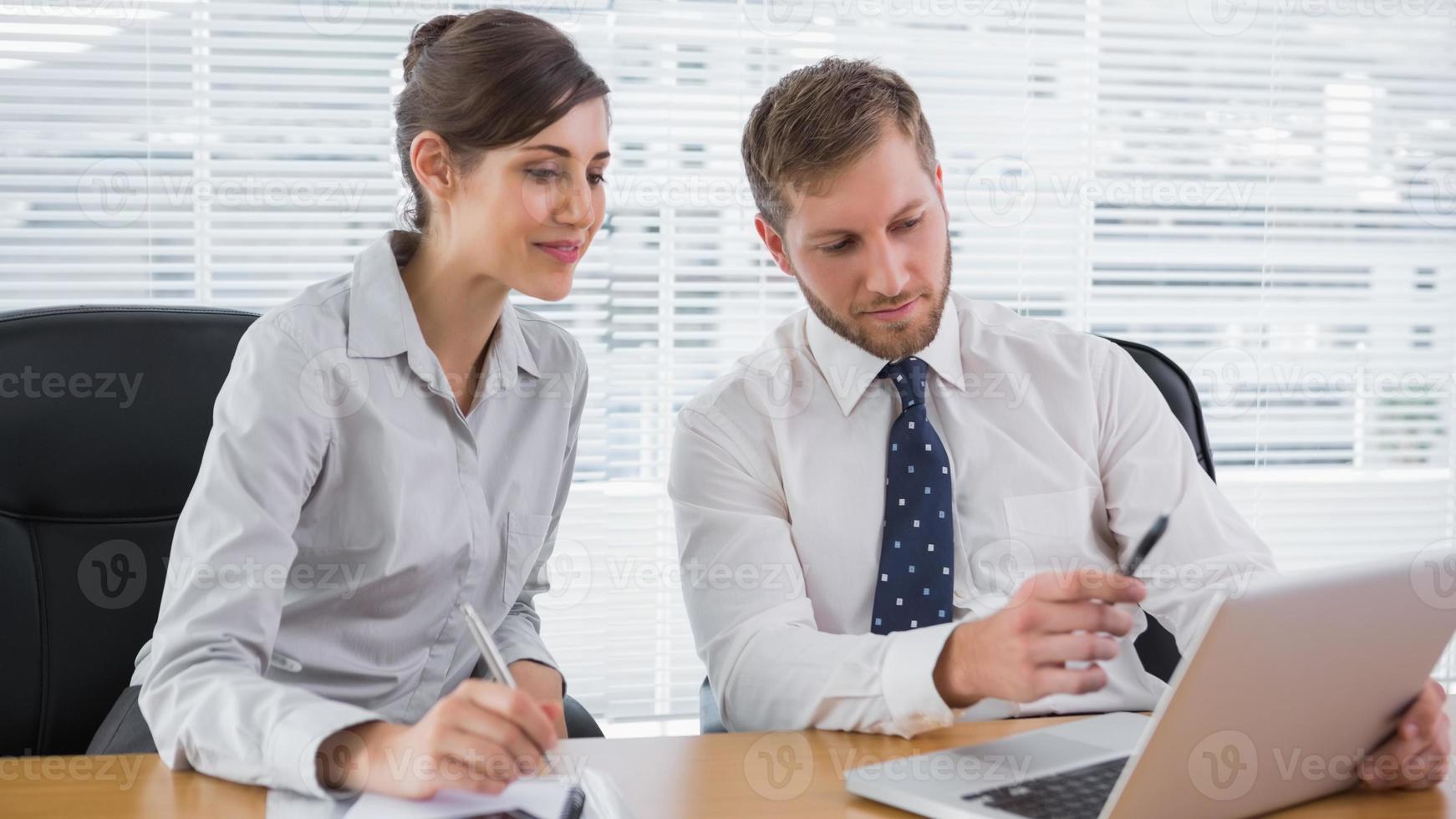 affärsmän som arbetar tillsammans med bärbar dator foto