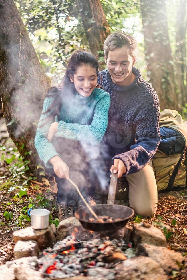 par matlagning på en lägereld i skogen foto