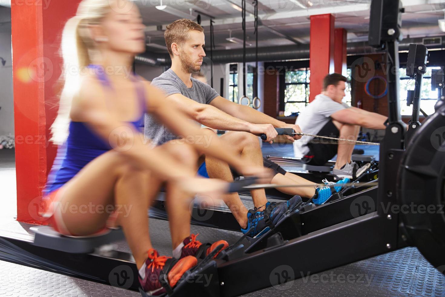 gymklass som tränar på roddmaskiner tillsammans foto