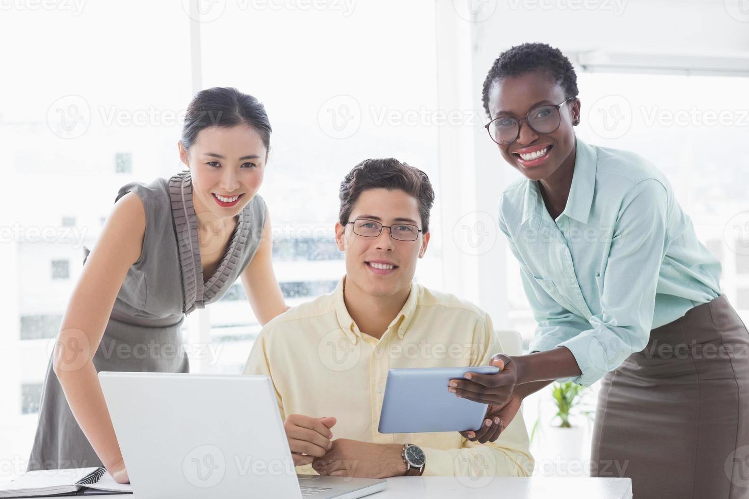 avslappnad affärsgrupp som tillsammans tittar på surfplattan foto
