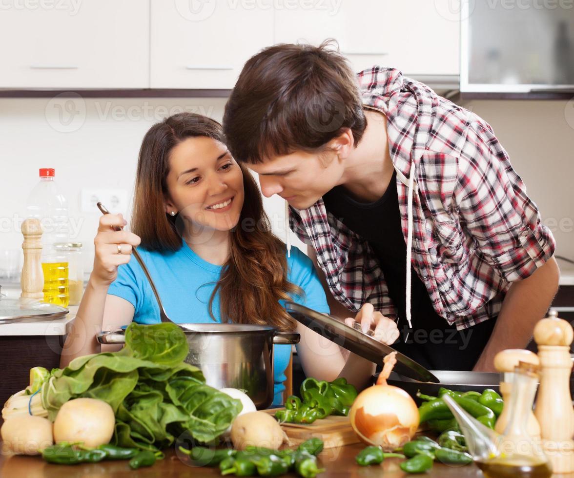 man och ung kvinna som lagar mat tillsammans foto