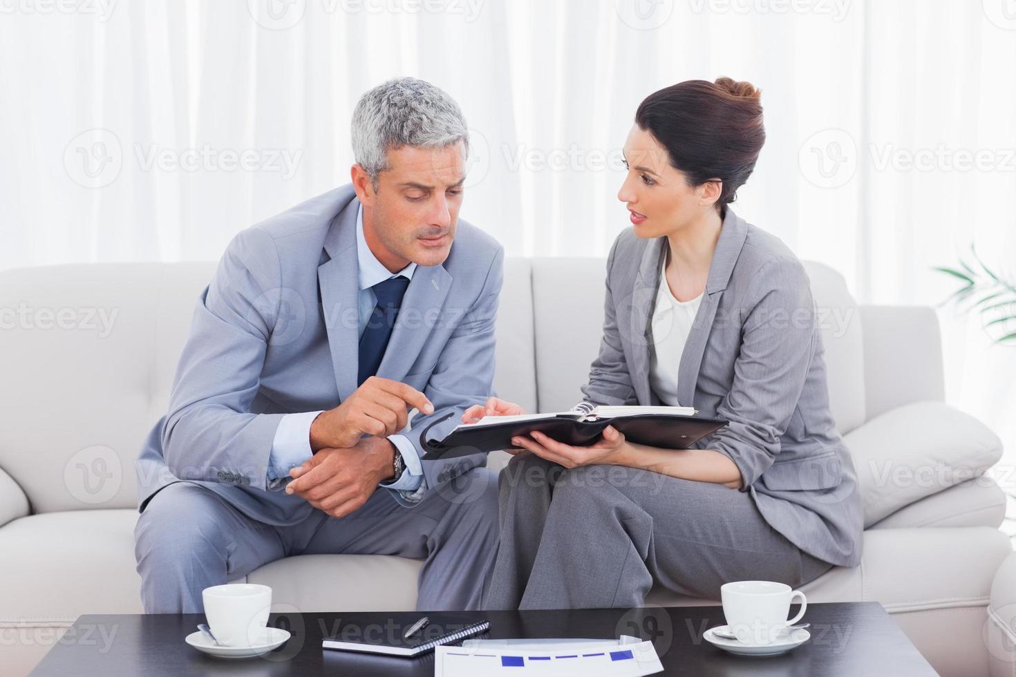 allvarliga affärsmän som arbetar och pratar tillsammans på soffan foto