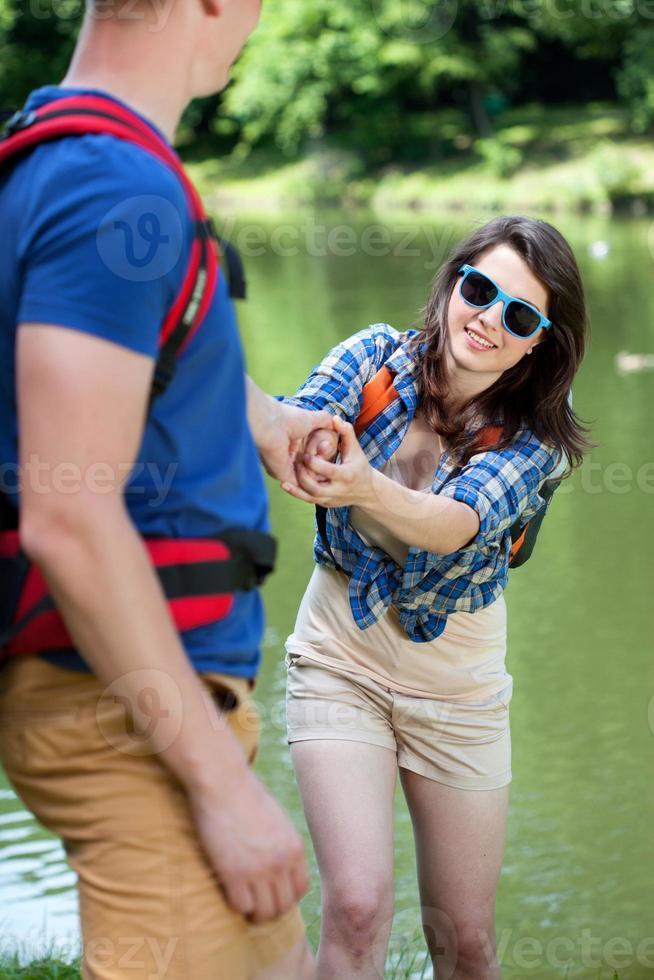 pojke som hjälper flickan vid sjön foto