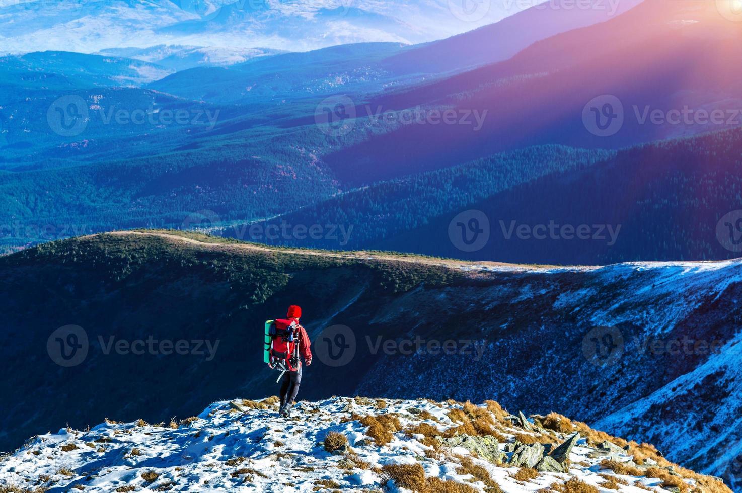 vandrare som går på snö sluttningsbergen och solen skiner foto