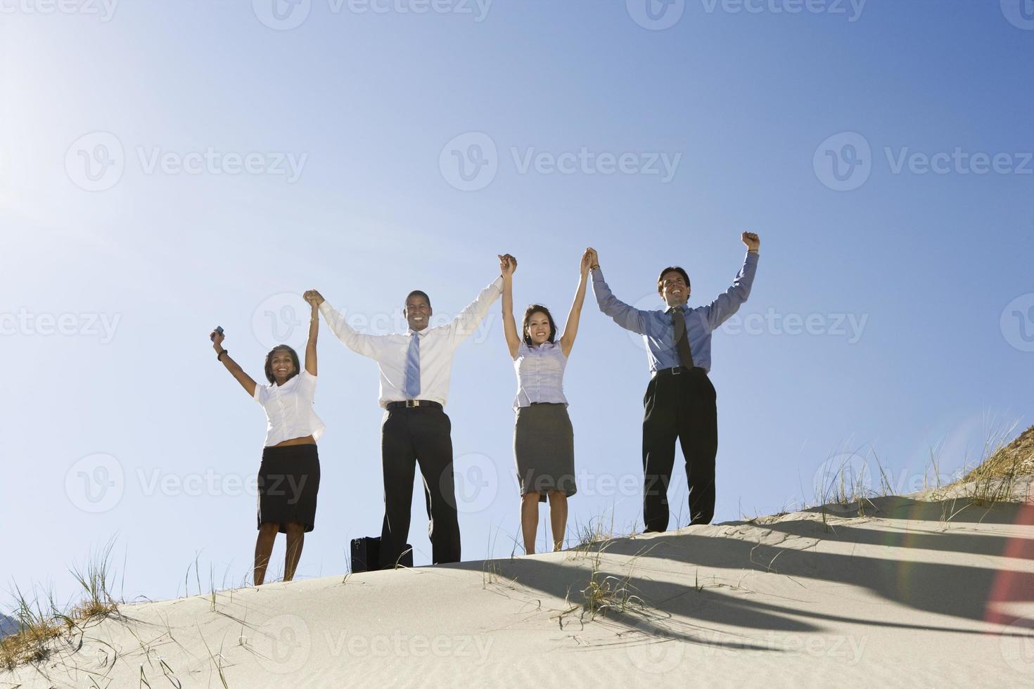 affärsmän som står tillsammans genom att höja handen foto