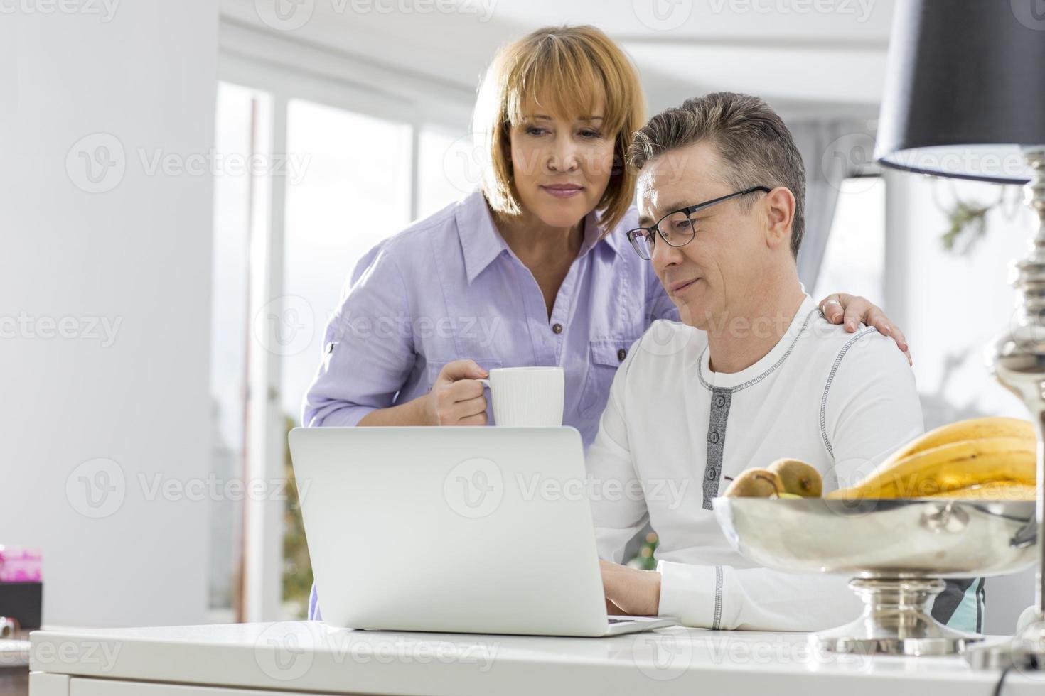 äldre par som använder bärbar dator tillsammans vid bordet i huset foto