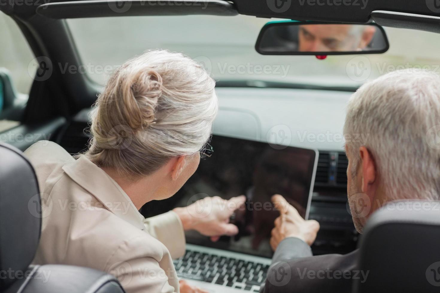 affärsmän som arbetar tillsammans på bärbar dator i stilrena cabriolet foto
