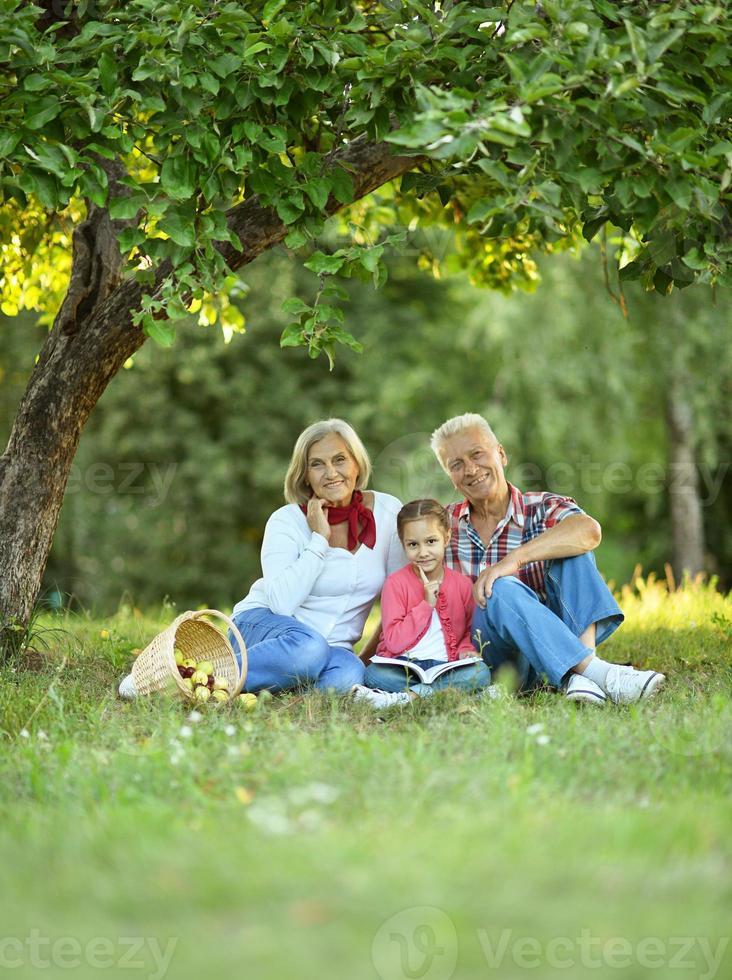 familj med äpplen och bok i park foto