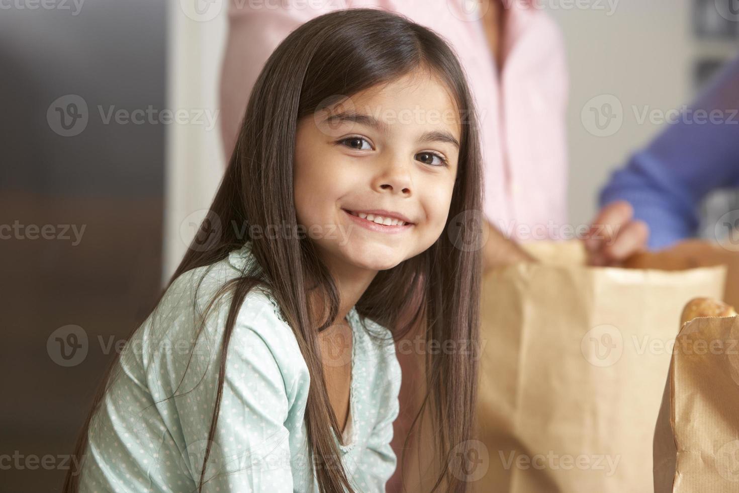 familj som packar upp livsmedelsbutiker i köket foto