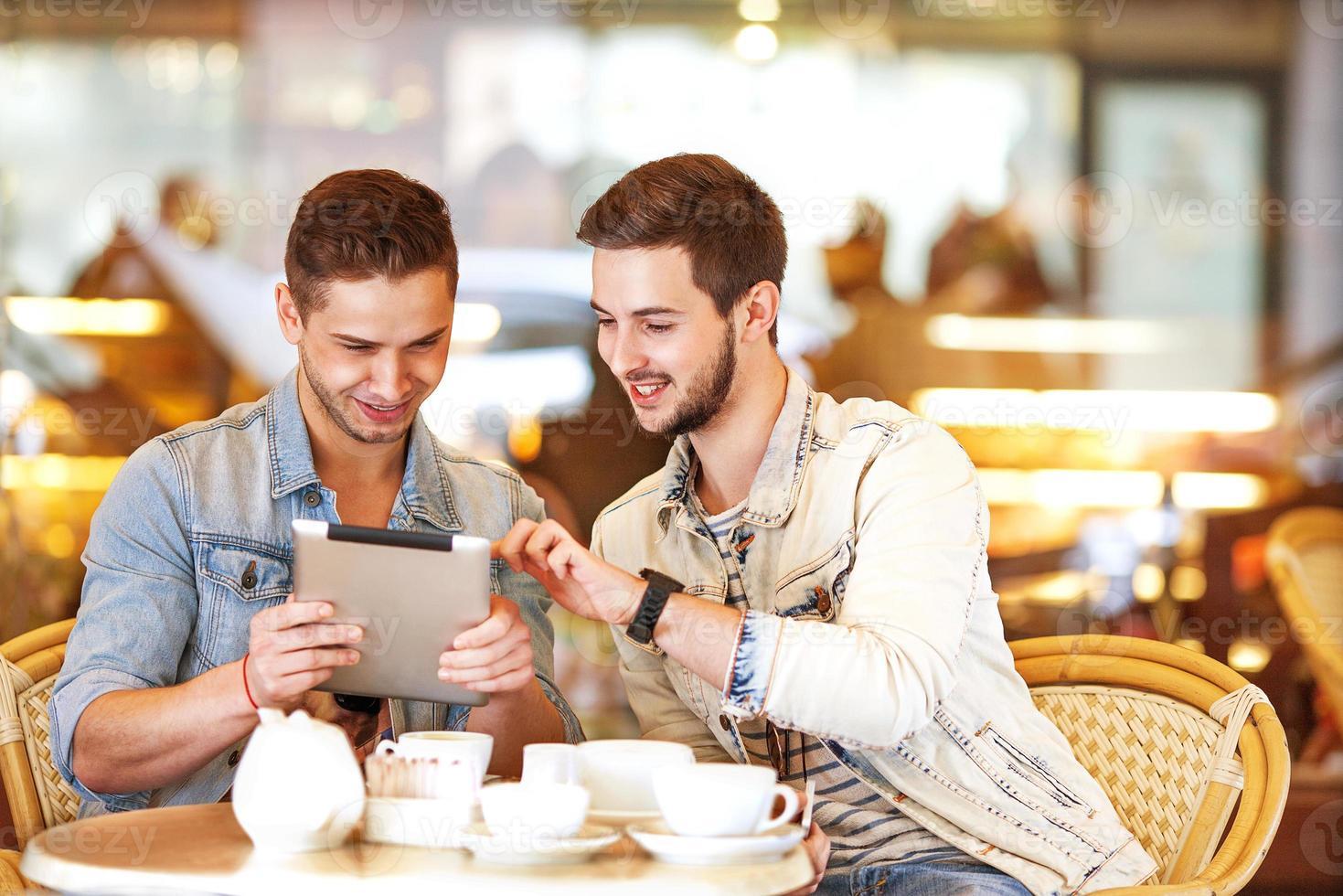 två unga män / studenter som använder surfplattan på café foto