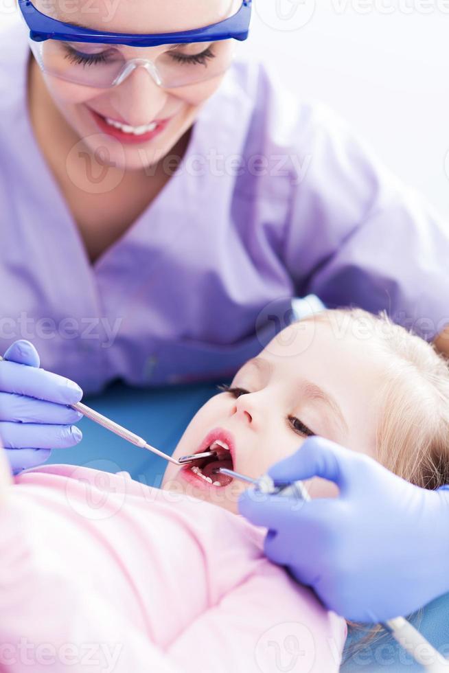 kvinnlig tandläkare som undersöker flicka foto