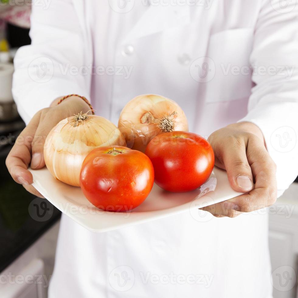 kocken presenterade lök och tomat foto