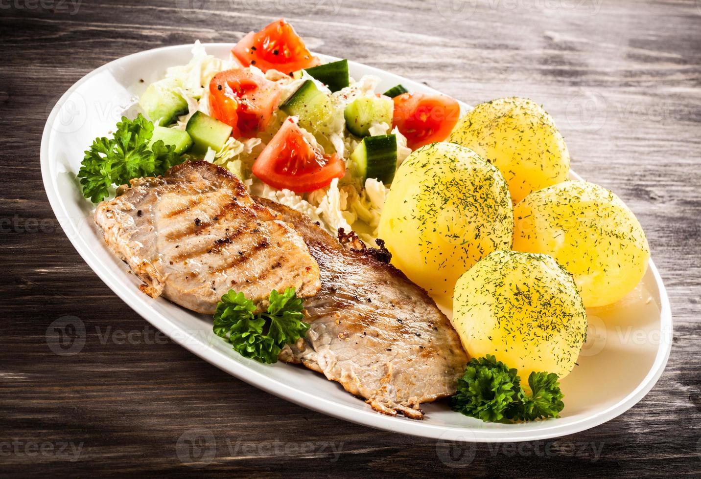 grillad biff, kokta potatis och grönsaker på träbakgrund foto