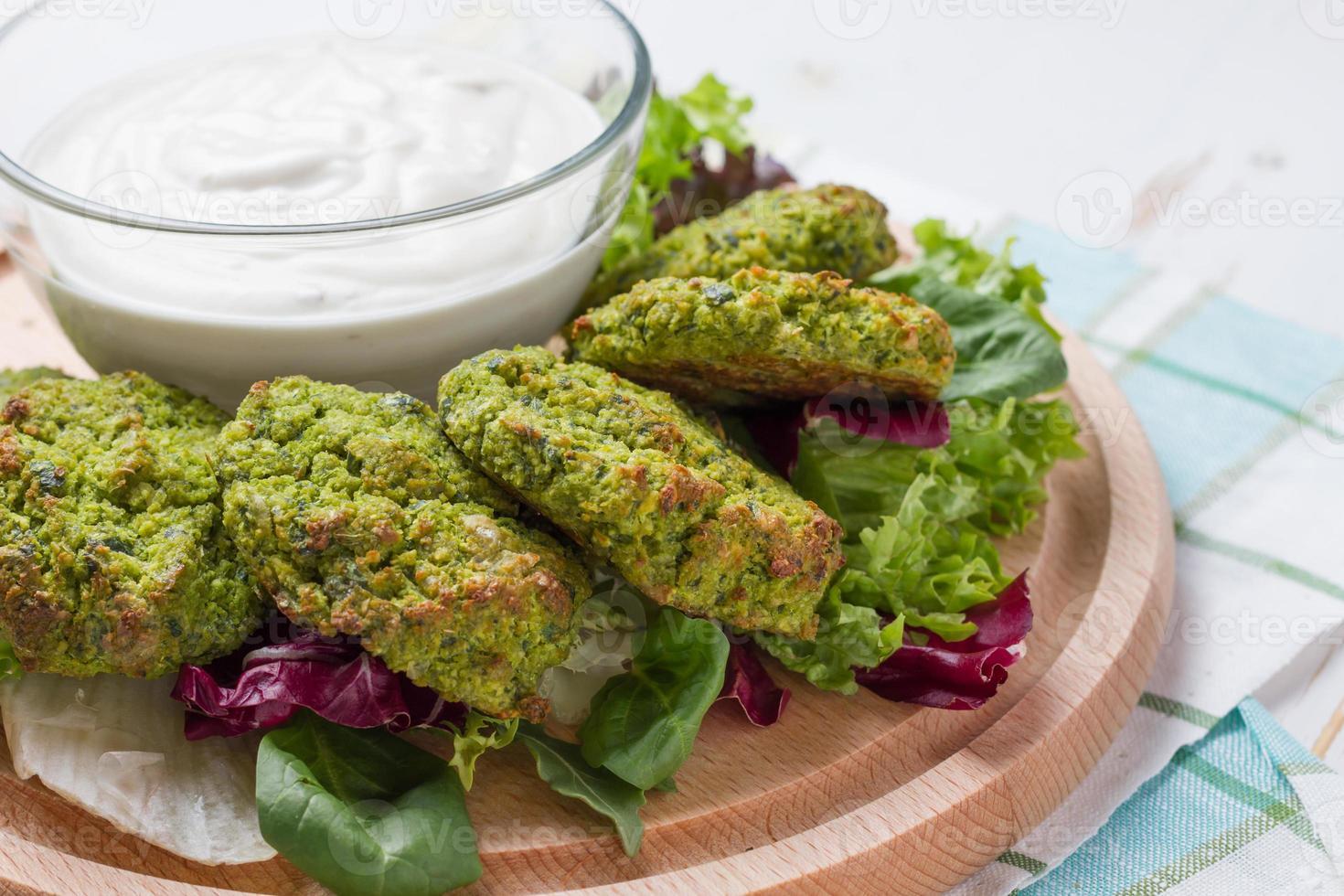 falafel serveras med tahinasås på träplatta foto