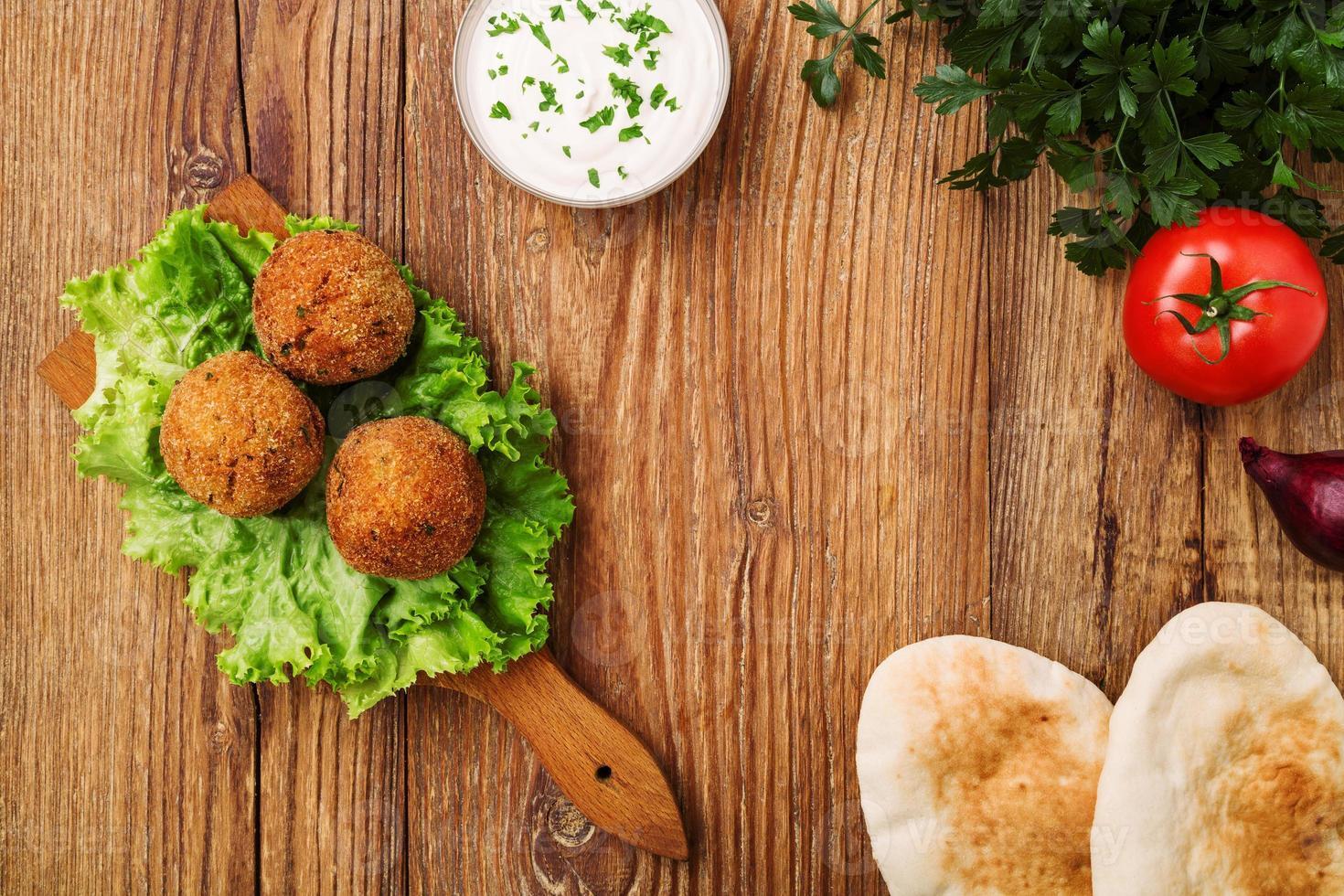 kikärta falafelbollar på ett träskrivbord med grönsaker foto