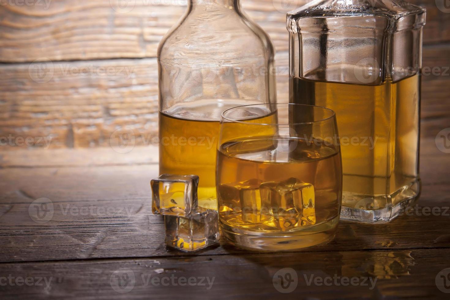 glas whisky med is på en träbakgrund foto
