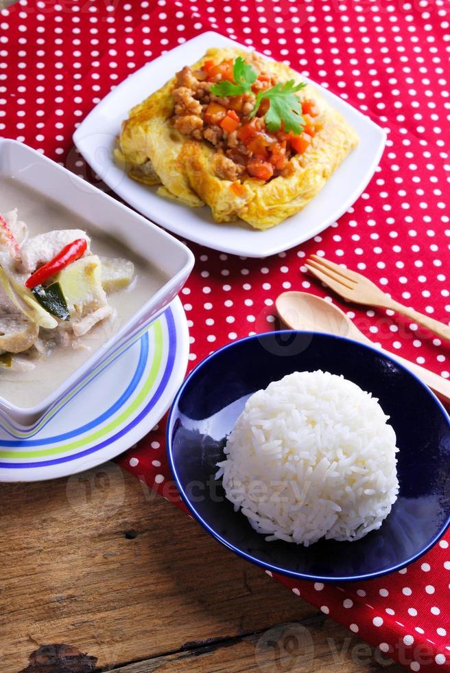 ris, fylld omelett och tom kha kai, kyckling med kokos foto
