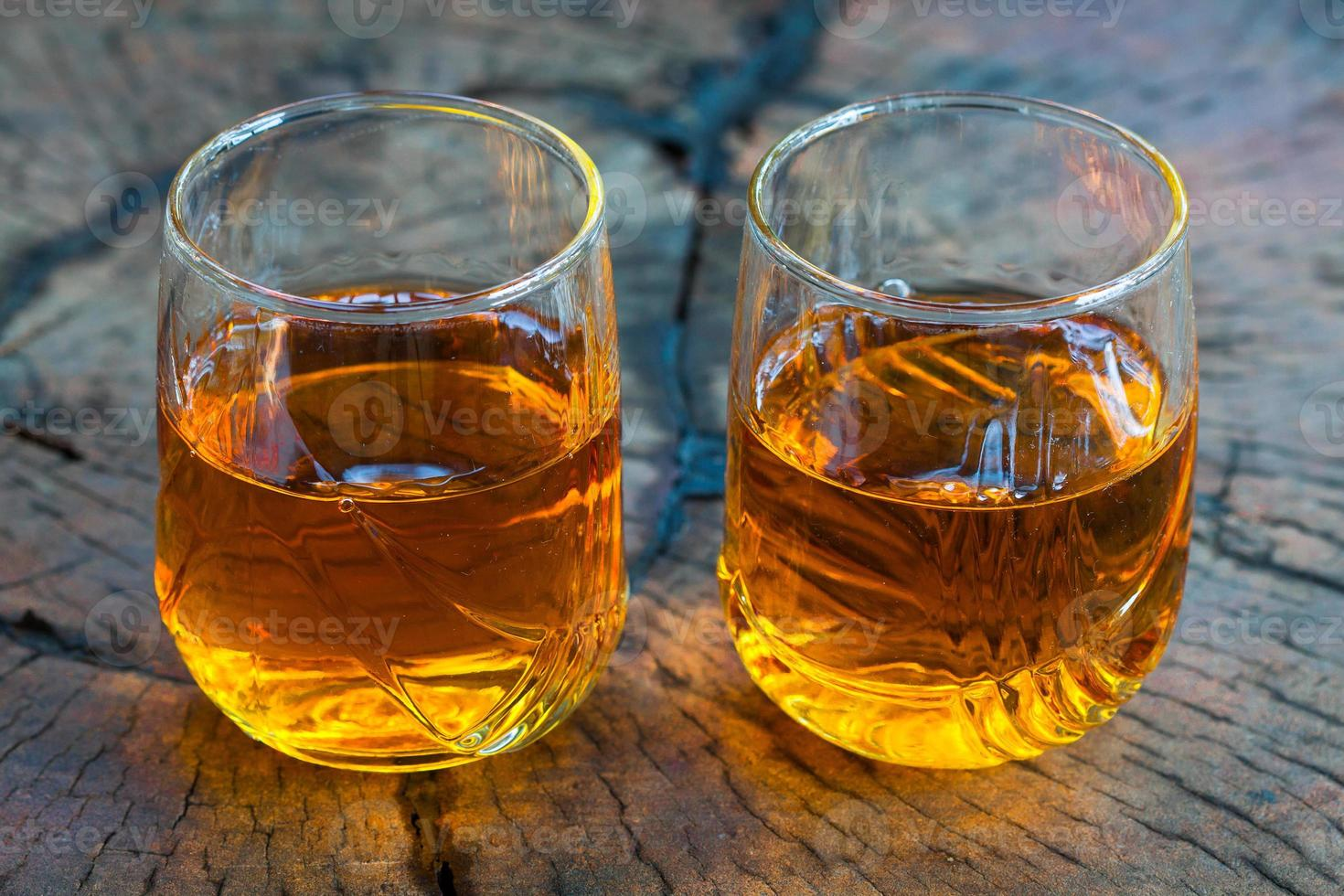 guldbrun whisky på klipporna i ett glas foto