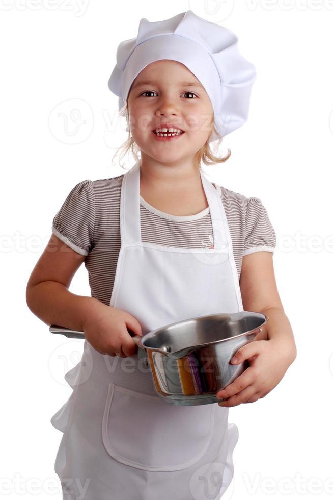 liten flicka klädd som en kock på en isolerad bakgrund foto