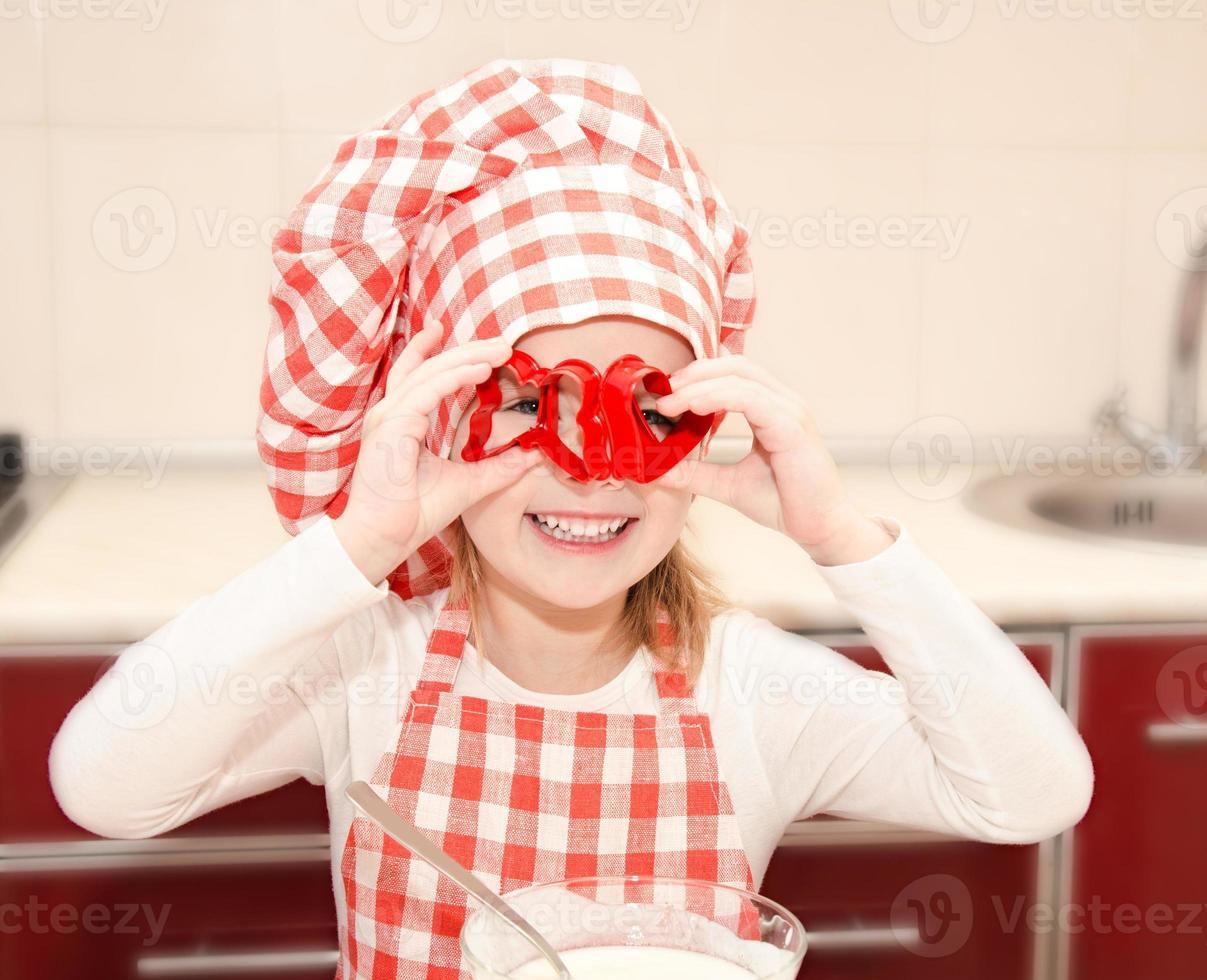 glad liten flicka som har kul med formen för kakor foto