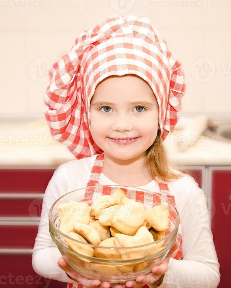 leende liten flicka i skålen som håller skålen med kakor foto