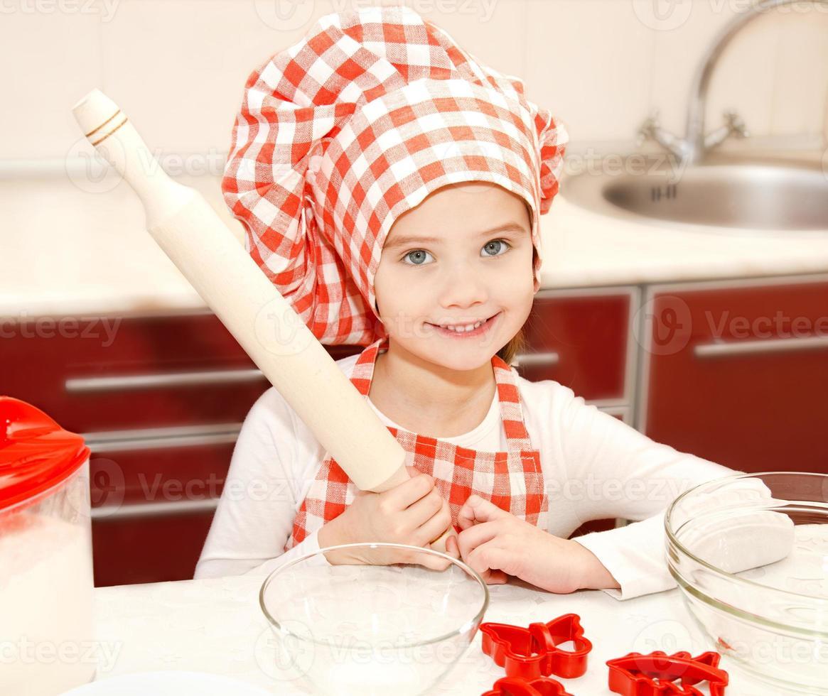 liten flicka med kockhatt och kavel foto
