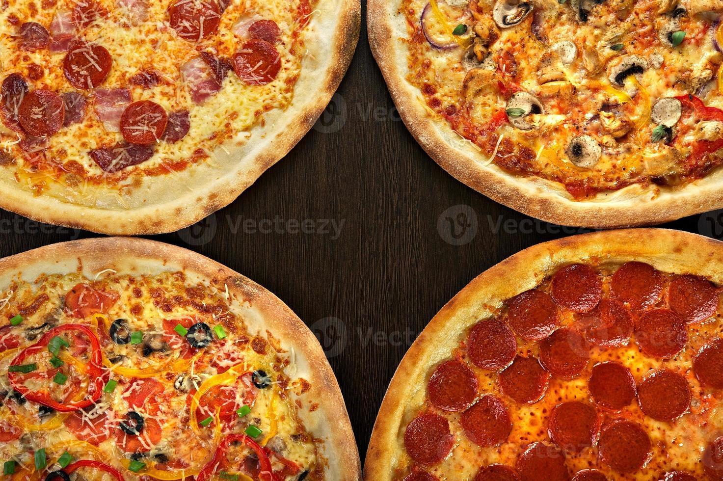 fyra pizza på en mörk träbakgrund foto