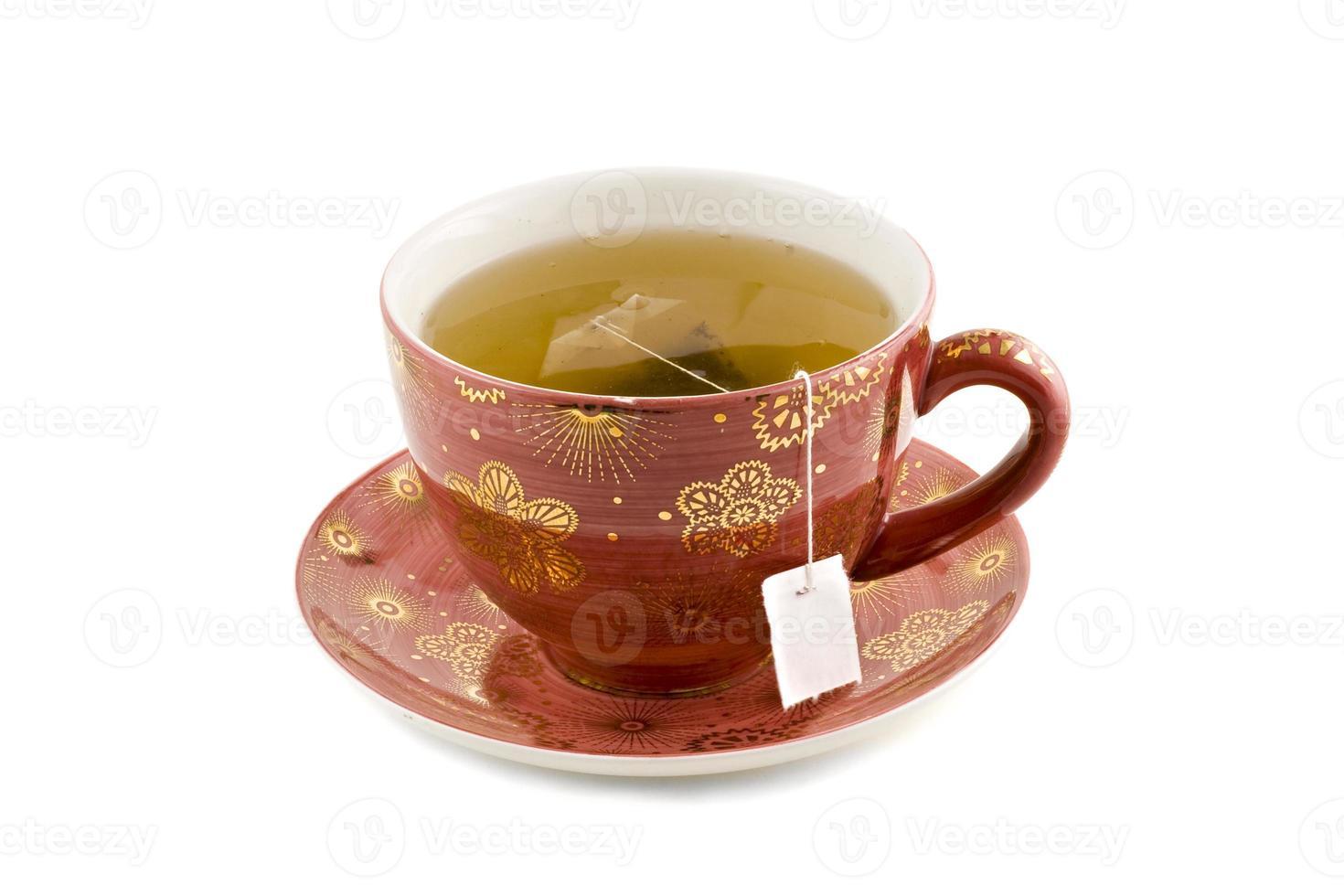 fin kopp te i en röd vintage uppsättning tekopp och tallrik foto