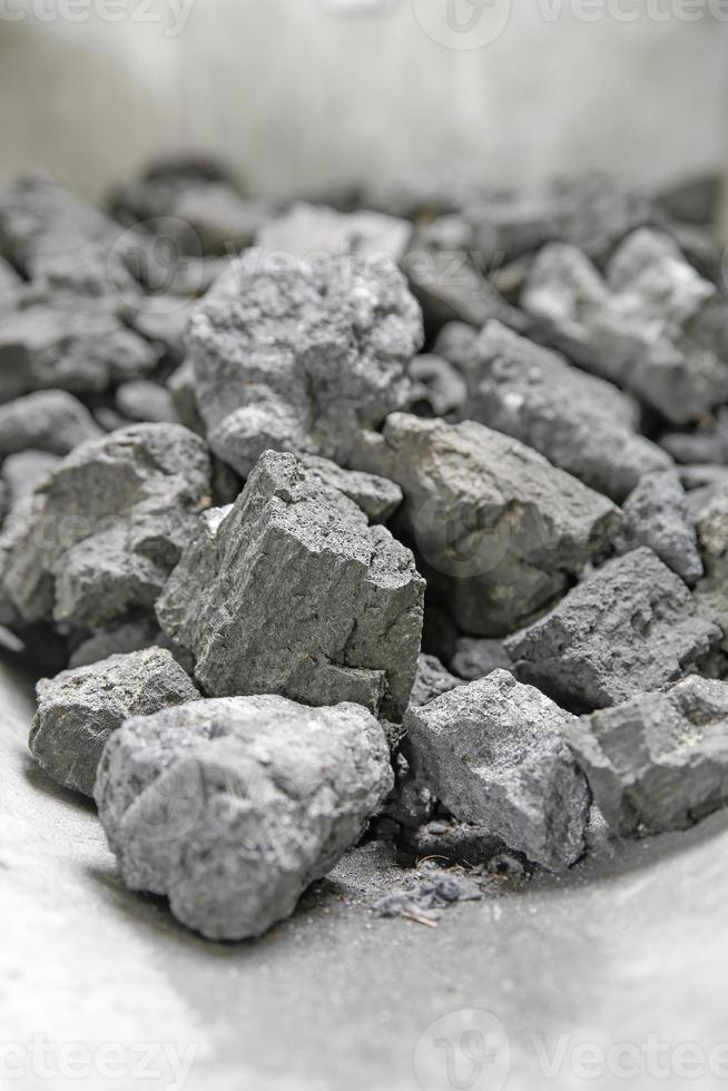 grå bitar av koks på en spade foto