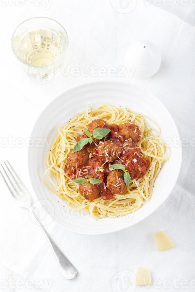 köttbullar i tomatsås och färsk basilika med spaghetti foto