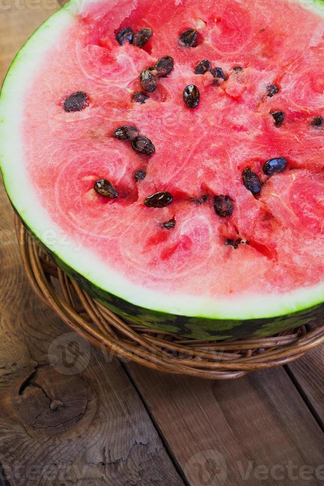 skär i halv vattenmelon på gamla träbord foto