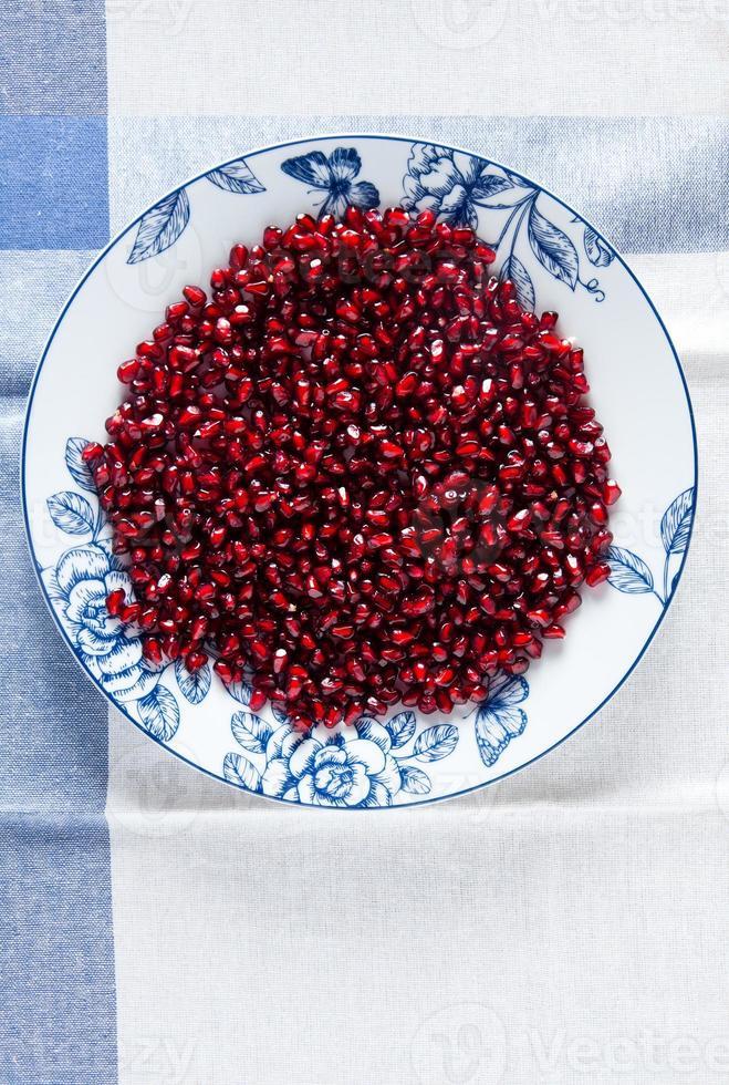 granatäpplefrön på plattan på vitt foto