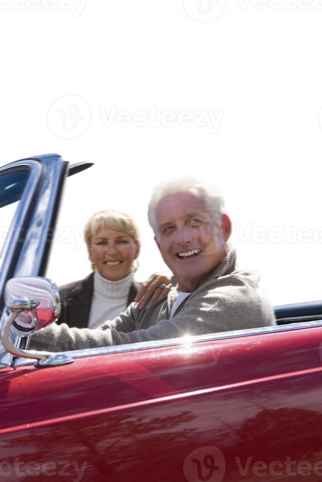 äldre par som sitter i röd öppen topp, klippt ut foto