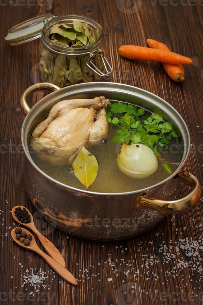 kycklingbuljong med grönsaker och kryddor i en kastrull foto