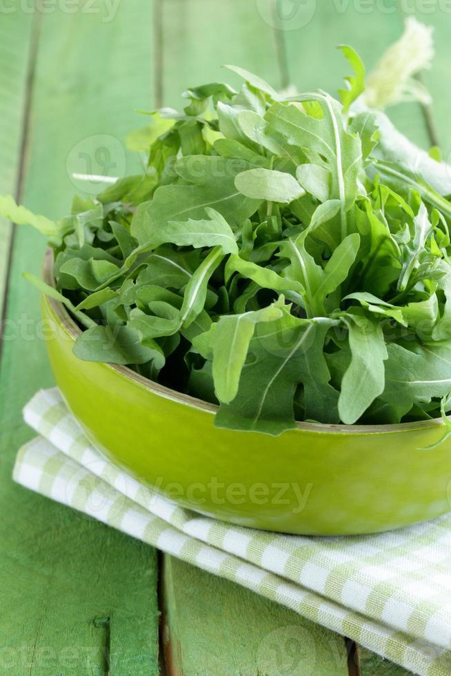 skål med grön sallad med ruccola på träbord foto