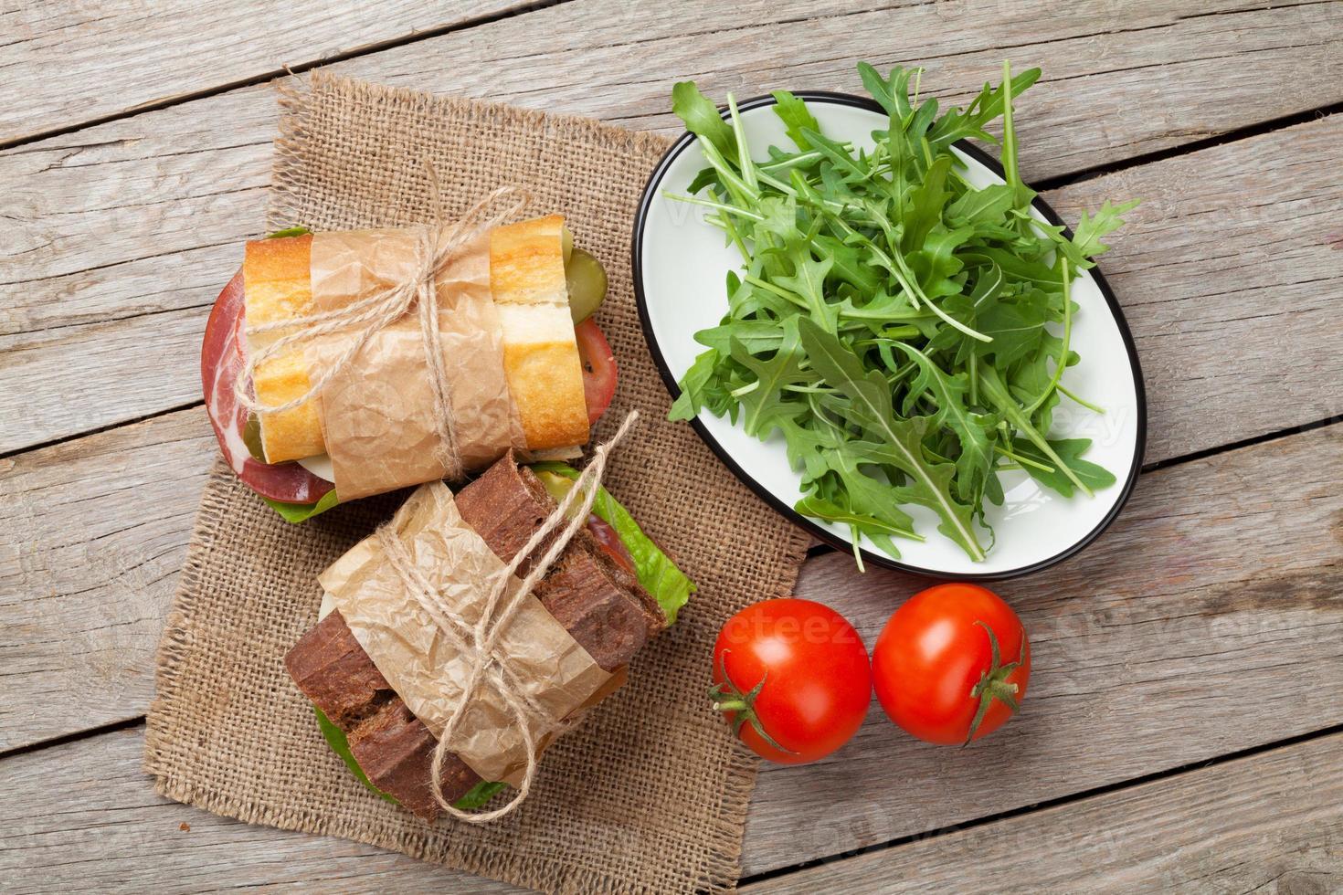 två smörgåsar med sallad, skinka, ost och tomater foto