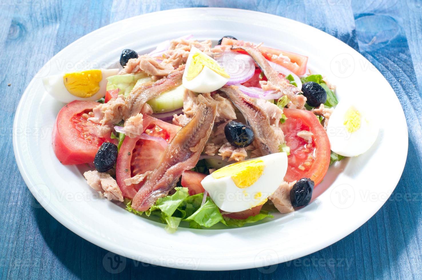 nicoisesallad med ägg, ansjovis, lök, sallad och tonfisk foto