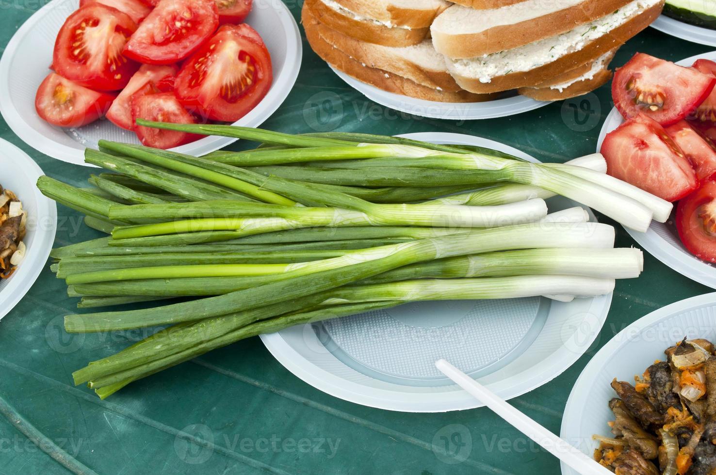gröna lökar på bordet foto