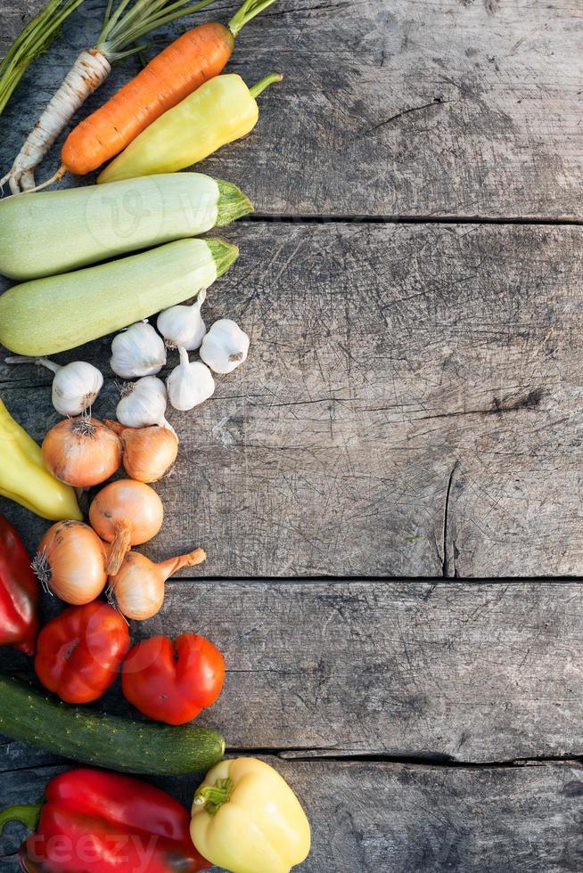 färska grönsaker på gammal träbakgrund foto